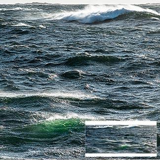 Aufgewühltes Meer mit hohen Wellen mit Inseln am Horizont